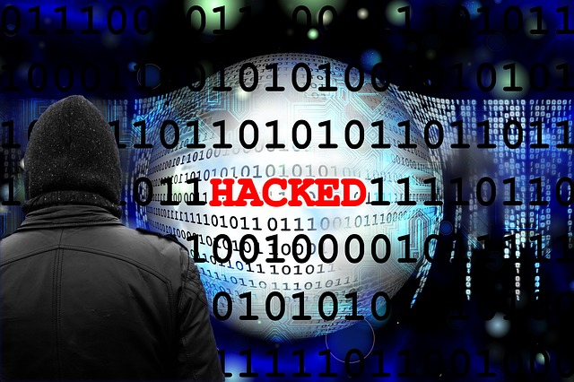 Man in hoodie facing of grid of numbers, zero's and one's, with red text reading 'HACKED' in the center.