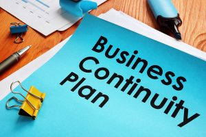 A document on a work desk with the words business continuity plan on the cover